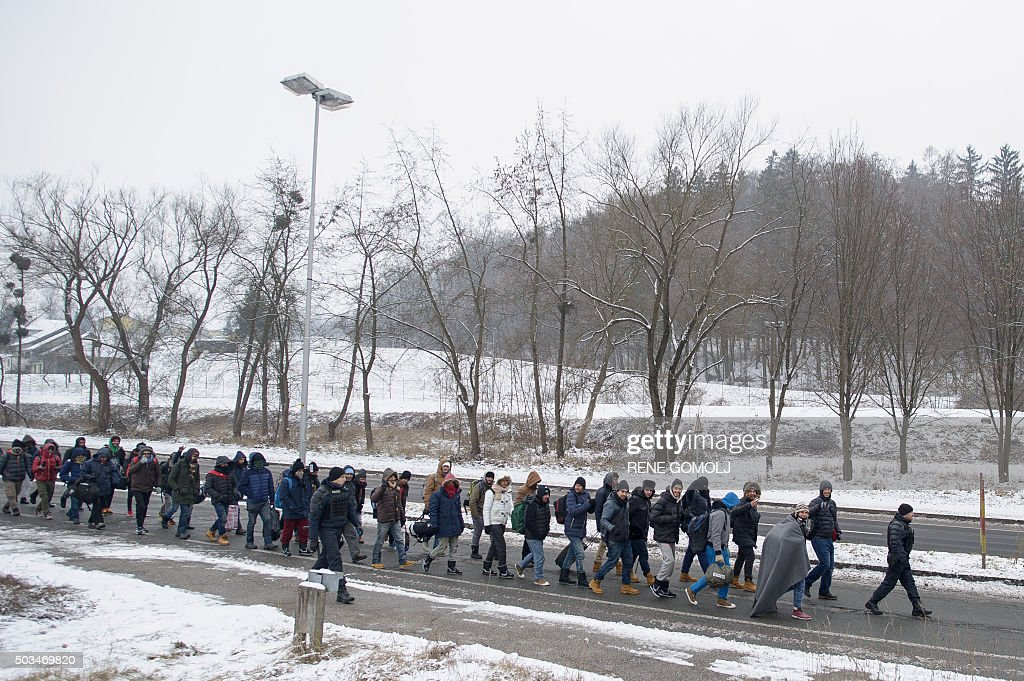 Refugees and migrants walk to cross the SlovenianAustrian border on January 5 2016 in Sentilj / AFP / Rene Gomolj