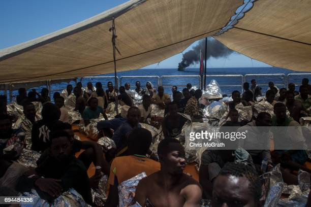 Refugees and migrants watch from onboard the Migrant Offshore Aid Station Phoenix vessel as a small rubber boat some of them were rescued from burns...