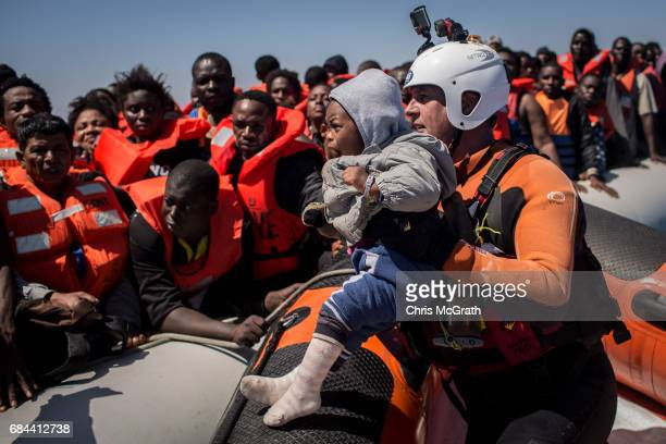 Refugees and migrants watch on from a rubber boat as a search and rescue crew member from the Migrant Offshore Aid Station Phoenix vessel helps a...