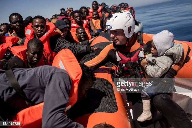 Refugees and migrants watch on from a rubber boat as a search and rescue crew member from the Migrant Offshore Aid Station Phoenix vessel helps a man...