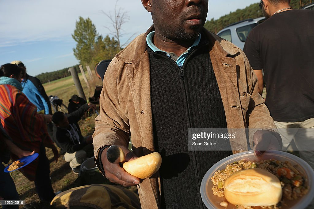 Refugees and supporters receive food while stopping for a rest in the hamlet of Neschholz during their protest march across nearly 600km from Wuerzburg to Berlin on October 2, 2012 near Bad Belzig, Germany. Approximately 25 refugees who are seeking political asylum are marching to protest the conditions under which they live in Germany. Asylum seekers in Germany are by law prohibited from working and their ability to travel is very restricted. The group expects to arrive in Berlin on October 6.