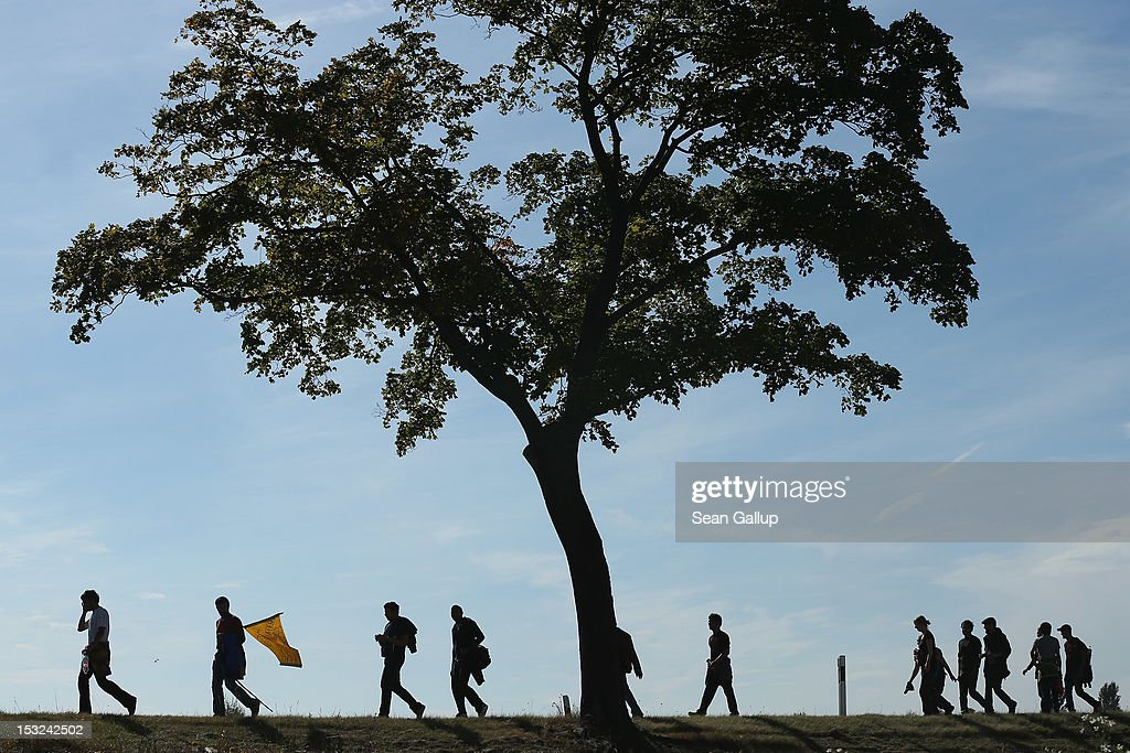 Refugees and supporters walk along a country road during their protest march across nearly 600km from Wuerzburg to Berlin on October 2, 2012 near Bad Belzig, Germany. Approximately 25 refugees who are seeking political asylum are marching to protest the conditions under which they live in Germany. Asylum seekers in Germany are by law prohibited from working and their ability to travel is very restricted. The group expects to arrive in Berlin on October 6.