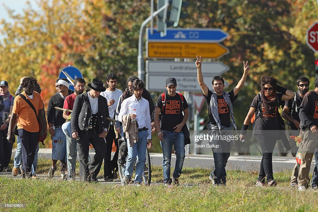 Refugees and supporters walk along a country road during their protest march across nearly 600km from Wuerzburg to Berlin on October 2, 2012 near Bad Belzig, Germany. Approximately 25 refugees from Iran, Iraq, Afghanistan, Turkey and other nations who are seeking political asylum are marching to protest the conditions under which they live in Germany. Asylum seekers in Germany are by law prohibited from working and their ability to travel is very restricted. The group expects to arrive in Berlin on October 6.