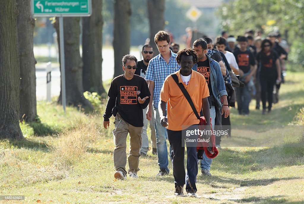 Refugees and supporters walk through the hamlet of Neschholz during their protest march across nearly 600km from Wuerzburg to Berlin on October 2, 2012 near Bad Belzig, Germany. Approximately 25 refugees who are seeking political asylum are marching to protest the conditions under which they live in Germany. Asylum seekers in Germany are by law prohibited from working and their ability to travel is very restricted. The group expects to arrive in Berlin on October 6.