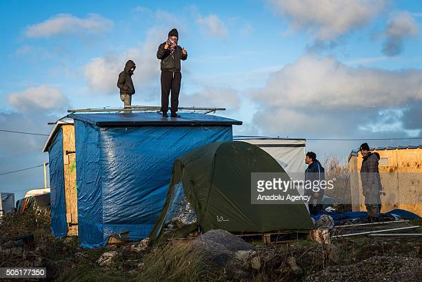 Refugees and volunteers work together to relocate huts in the camp known as the Jungle on January 15 2015 in Calais France French police have given...