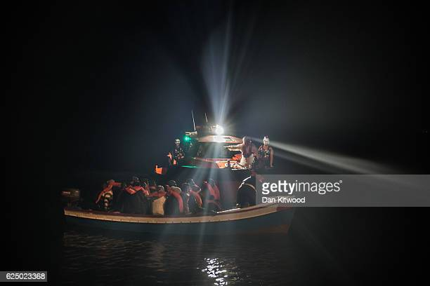 Refugees are escorted to the Topaz Responder in a wooden boat as members of MOAS Migrant Offshore Aid Station make rescues at sea on November 22 2016...