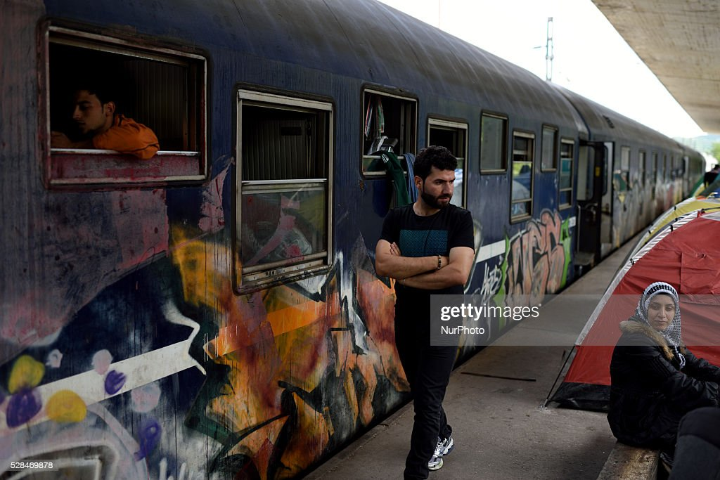 Refugees are seen on the dock of the train station next to an abandoned train cabin at Idomeni refugee camp on May 5'th, 2016. Thousands of migrants are still located in the makeshift refugee camp, located at the Greek Macedonian border, waiting for the border to re-open.