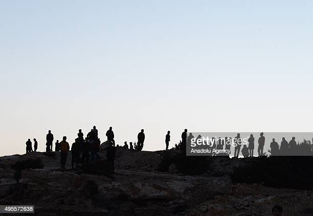 Refugees are seen on the top of a hill before they set off on a journey to Greece's Chios Island from the Cesme District of Izmir Turkey on November...