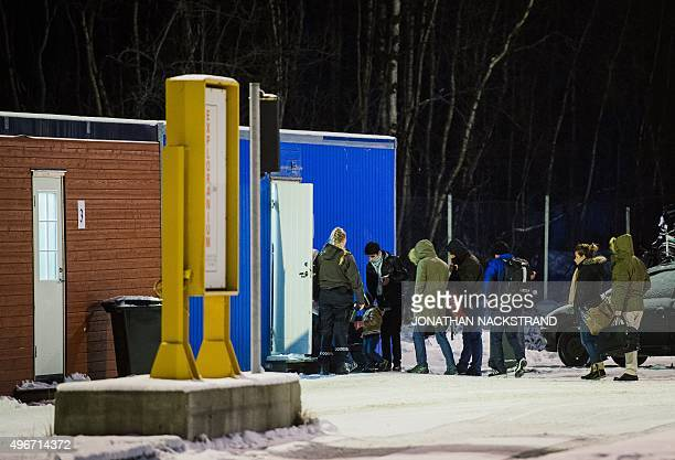 Refugees are welcomed upon arrival at the Norwegian border crossing station at Storskog after crossing the border from Russia on November 11 2015 An...