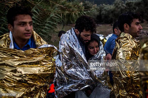 Refugees are wrapped with thermal blankets to shelter from cold as they arrived with others on the shores of the Greek island of Lesbos after...