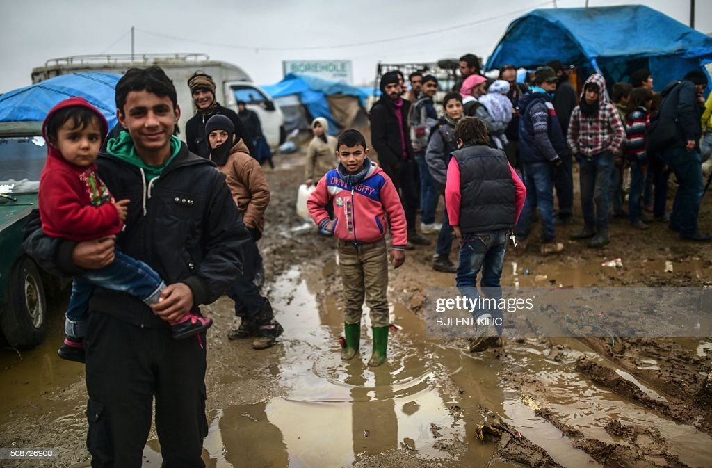Refugees arrive at the Turkish border crossing gate as Syrians fleeing the northern embattled city of Aleppo wait on February 6, 2016 in Bab-Al Salam, near the city of Azaz, northern Syria. Thousands of Syrians were braving cold and rain at the Turkish border Saturday after fleeing a Russian-backed regime offensive on Aleppo that threatens a fresh humanitarian disaster in the country's second city. Around 40,000 civilians have fled their homes over the regime offensive, according to the Syrian Observatory for Human Rights monitor. / AFP / BULENT KILIC