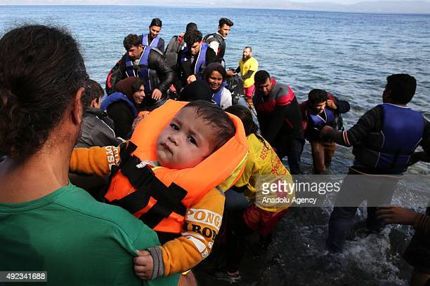 Refugees arrive by a rubber boat on the Greek island of Lesbos after crossing the Aegean sea on October 12 2015 Refugees who begin a journey with a...