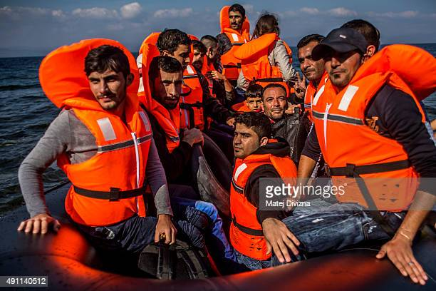 Refugees arrive on the shores of the Greek island of Lesbos after crossing the Aegean sea from Turkey on an inflatable boat on October 3 2015 near...