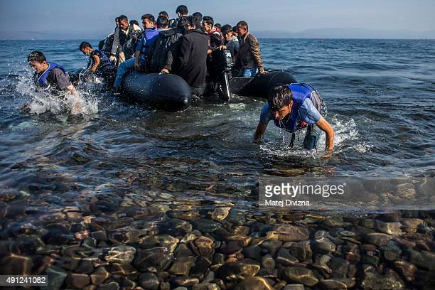 Refugees arrive on the shores of the Greek island of Lesbos after crossing the Aegean sea from Turkey on an inflatable boat on October 4 2015 near...