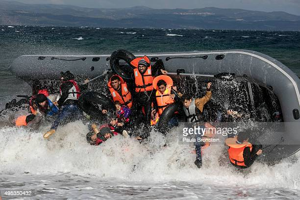 Refugees arriving to the island of Lesbos fall out of a boat as it capsizes landing in rough seas coming from Turkey on October 31 2015 in Lesbos...