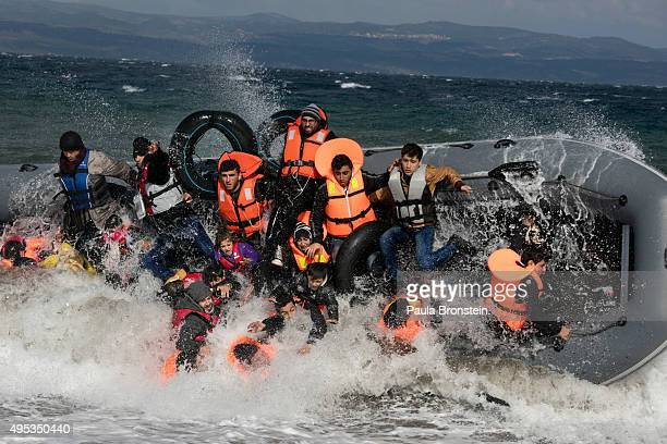 Refugees arriving to the island of Lesbos fall out of a boat as it capsizes on landing in rough seas coming from Turkey on October 31 2015 in Lesbos...