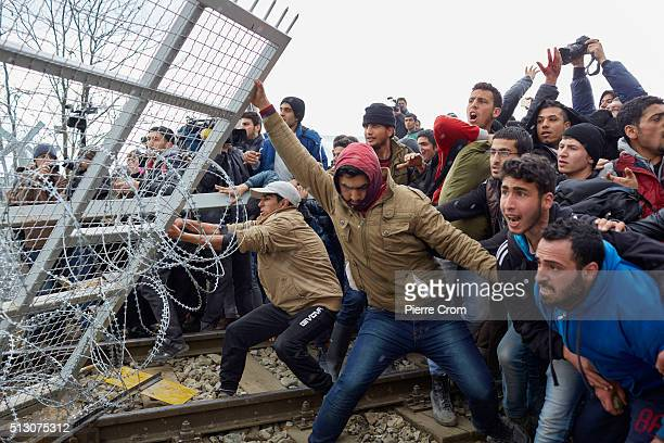 Refugees break the fence on the GreekMacedonia border on February 29 2016 in Idomeni Greece A group of refugees forced the gate in an attempt to...