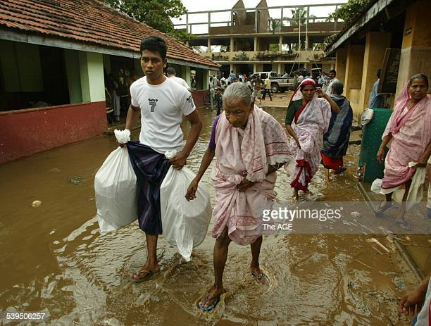 Refugees carry Aid Packages through the flooded waters of the camp in the Ampara district on the East coast of Sri Lanka 2 January 2005 THE AGE...
