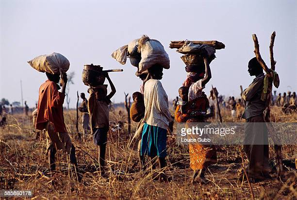 Refugees carry their belongings to the site of their new home in an open field in Camacupa Angola After Angola gained independence from Portugal in...