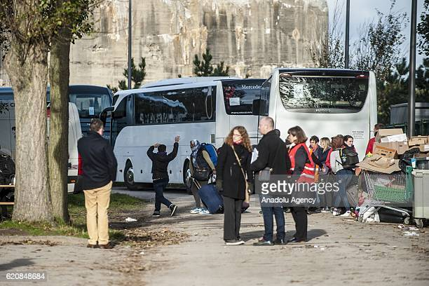 Refugees carry their luggages as they walk to climb into a bus after leaving the 'Jules Ferry' center reception in Calais on November 3 2016 Over 350...