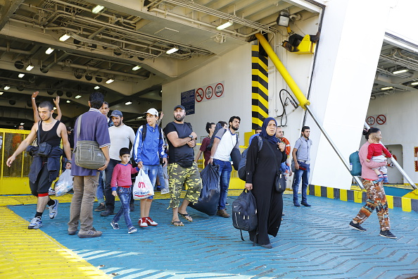 Refugees disembark from the El Venizelos ferry that has...