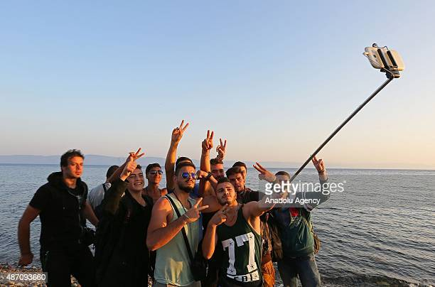 Refugees flash victory sign as they pose for a selfie on the shore of Eftalou beach north of the port city of Mytilini after crossing the Aegean from...