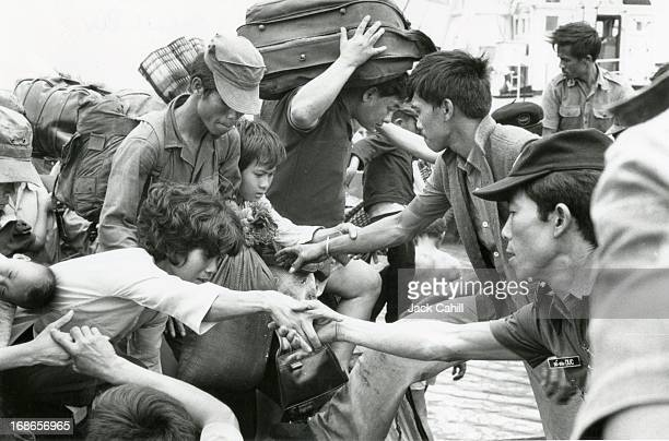 Refugees fleeing Saigon disembark from a barge