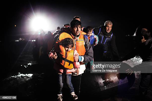 Refugees from Afghanistan and Syria arrive on a rubber boat with assistance of a fishing boat and the search light of a Greek coast guard vessel at...