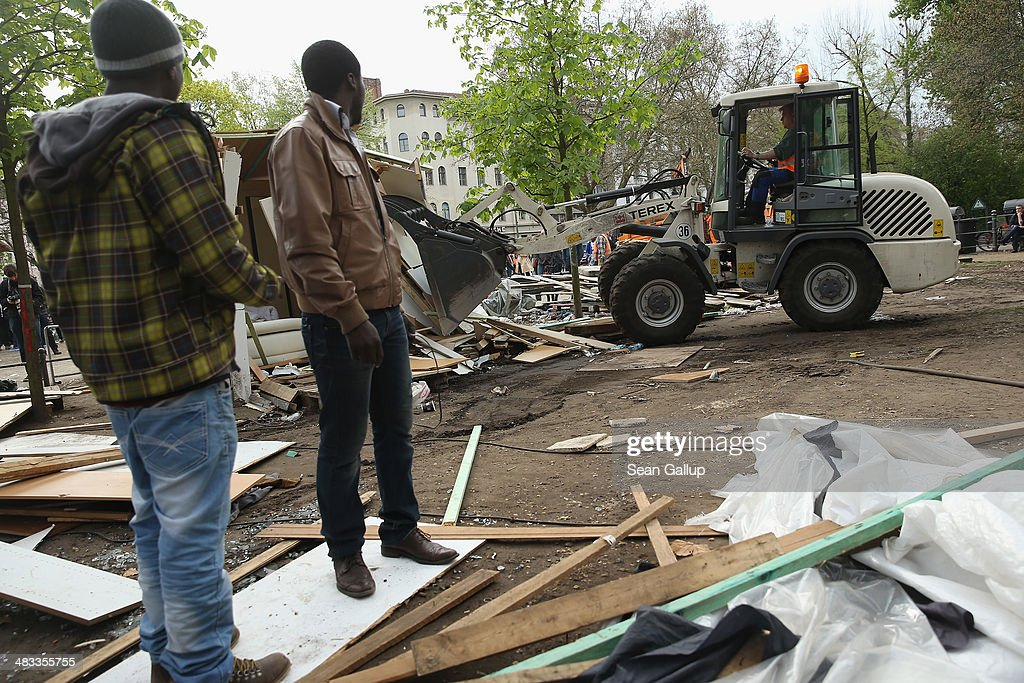 Refugees from Africa watch as a wheel loader demolishes huts that were being torn down at a temporary, city-tolerated refugee camp at Oranienplatz in Kreuzberg district on April 8, 2014 in Berlin, Germany. Refugees, many of them from Africa who came to Germany via Lampedusa, began dismantling their shelters today after many of them agreed to a deal with city authorities to move to a renovated hostel. Not all of the several hundred refugees, some of whom have been living at the Oranienplatz camp almost a year, have agreed to the deal, and while some said they will go elsewhere, some insist they will stay, despite a city order to vacate.