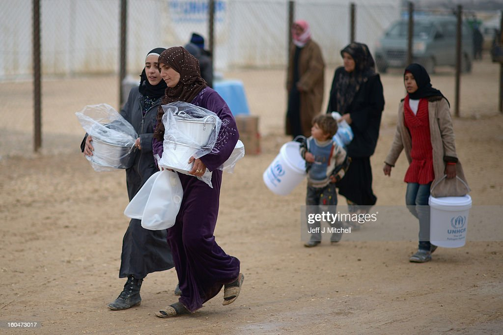 Refugees from Syria collect food and supplies from the UNHCR as they arrive at the Za'atari refugee camp on February 1, 2013 in Za'atari, Jordan. Record numbers of refugees are fleeing the violence and bombings in Syria to cross the borders to safety in northern Jordan and overwhelming the Za'atari camp. The Jordanian government are appealing for help with the influx of refugees as they struggle to cope with the sheer numbers arriving in the country.