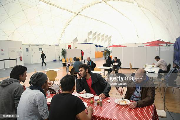 Refugees from Syria eat lunch in the cafeteria area in an inflatable hall that serves as temporary housing for refugees and migrants seeking asylum...