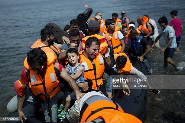Refugees from Syria land on the shores of the Greek island of Lesbos aboard an inflatable dinghy across the Aegean Sea from from Turkey on September...