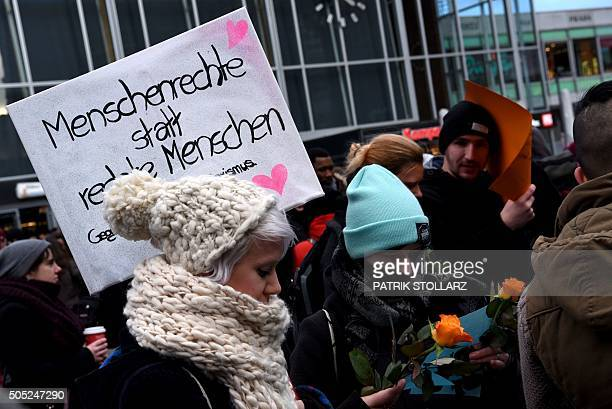 Refugees from Syria present flowers to passersby as they demonstrate against violence near the Cologne main train station in Cologne western Germany...