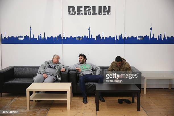 Refugees from Syria relax in an inflatable hall that serves as temporary housing for refugees and migrants seeking asylum in Germany as a child plays...