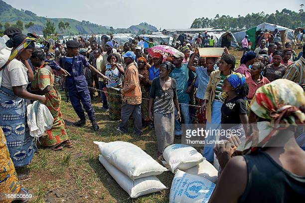 Refugees from the war in Congo gets meal during a food distribution in camp Butembo for displaced persons on January 23 2013 in Goma Democratic...