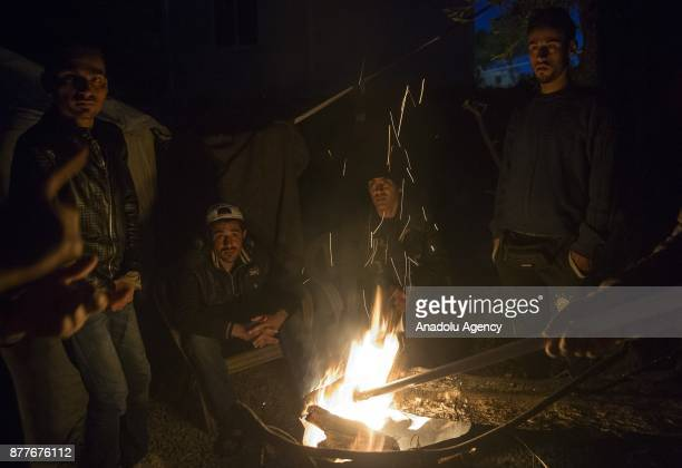 Refugees gather around a fire at the Moria Refugee Camp in Lesbos Greece on November 21 2017 Overpopulated refugee camp is comprised mostly of...