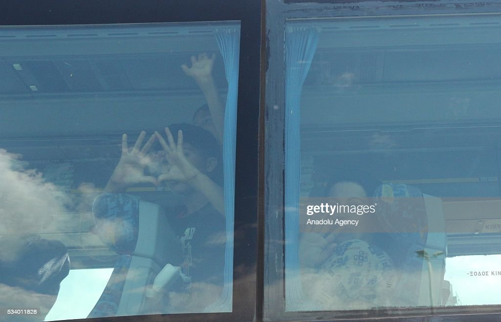 Refugees gestures on a bus as Greek police began to evacuate the makeshift refugee camp at the Greek-Macedonian border near the northern Greek village of Idomeni on May 24, 2016.
