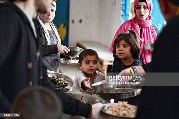 Refugees get meal cooked by chef Talal Rankoussi and volunteers outside the 'Cafe Rits' in Ritsona refugee camp some 80 km north of Athens on...