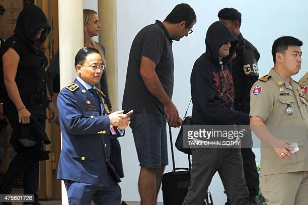 Refugees held under Australian custody in the Central Pacific island of Nauru are escorted by Cambodian police following their arrival at the Phnom...