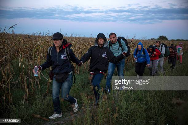 Refugees including a disabled boy from Syria are smuggled through fields and forests in an attempt to evade the Hungarian police close to the Serbian...