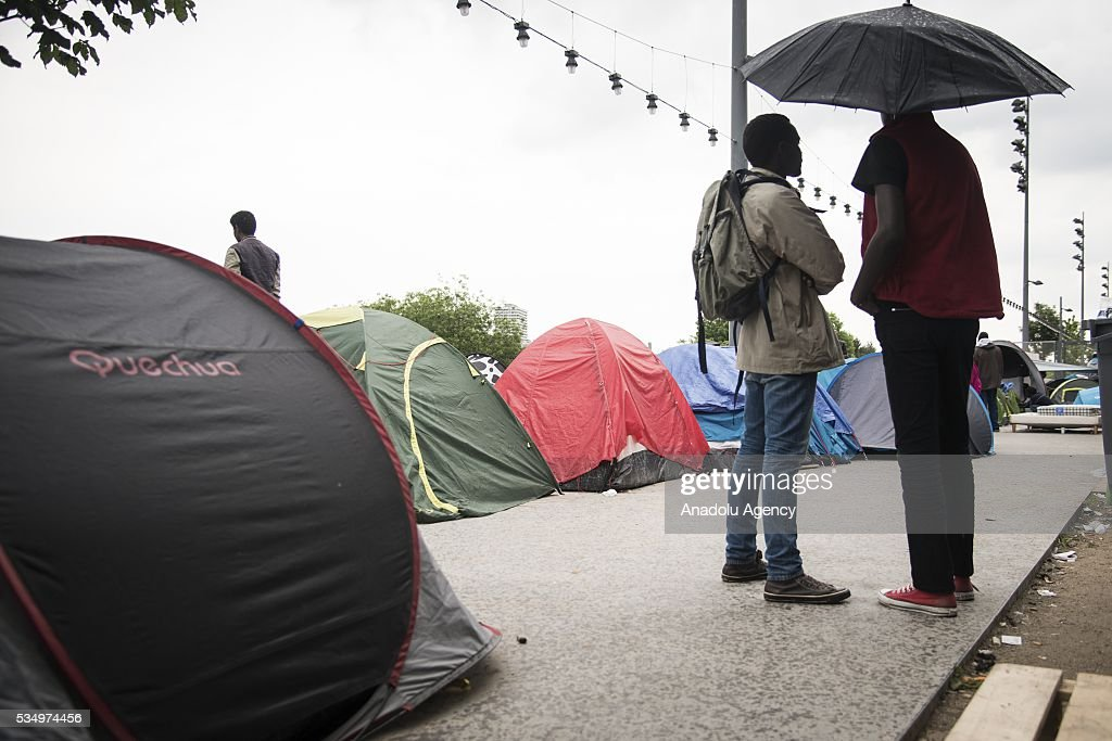 Refugees live in harsh conditions at a makeshift camp set at the Jardin d'Eole in Paris on May 28, 2016.