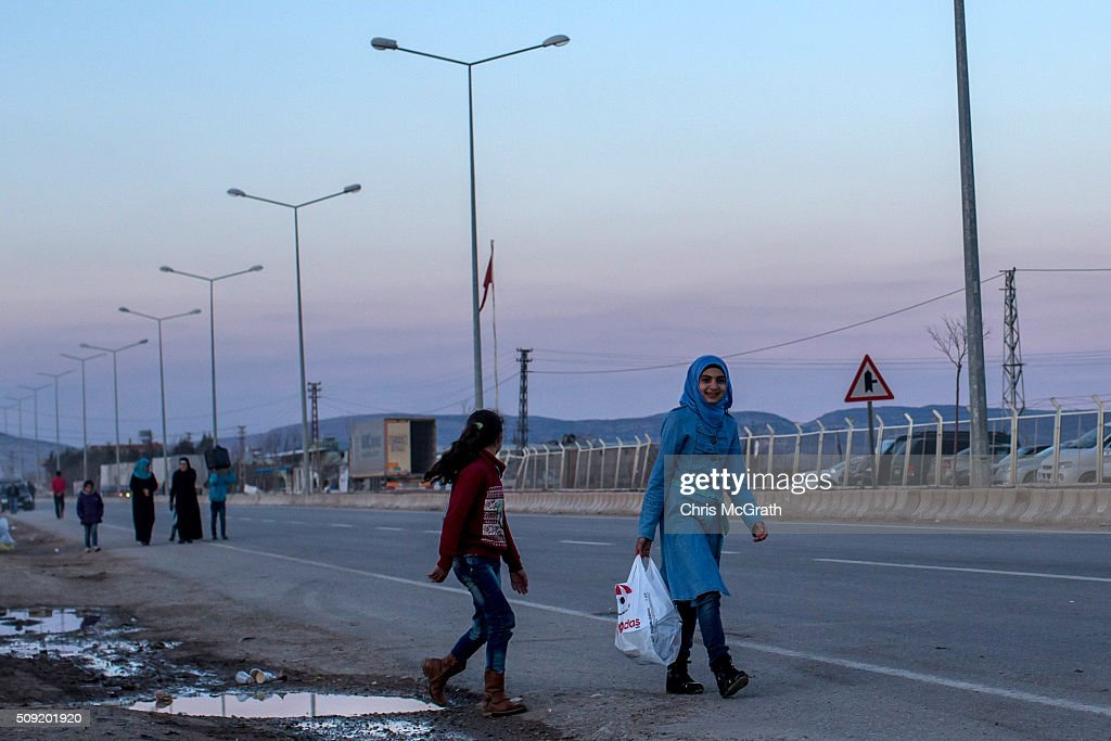 Refugees living in the Kilis refugee camp are seen walking along the road at the closed Turkish border gate on February 9, 2016 in Kilis, Turkey. According to Turkish officials some 35,000 Syrian refugees have massed on the Syrian/Turkish border after fleeing Russian airstrikes and a regime offensive surrounding the city of Aleppo in northern Syria. Turkey's President Recep Tayyip Erdogan said Turkey would open it's doors' if necessary'.