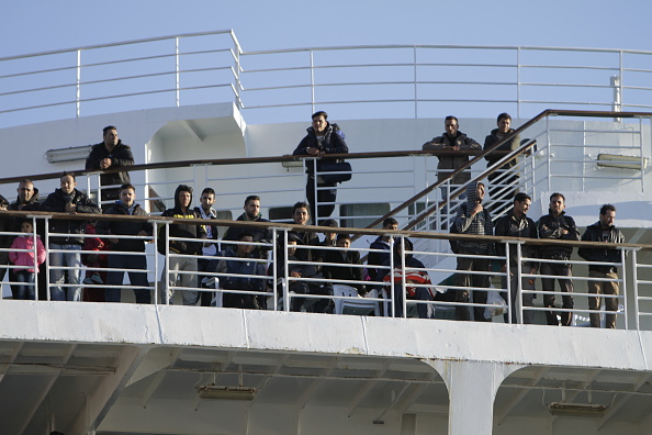 Refugees look down from the railings of the ferry EL.