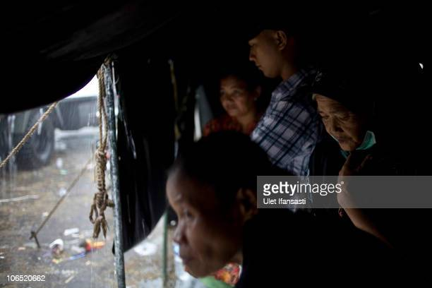 Refugees look out from inside a tent during rain at a temporary evacuation center set up as a result of the repeated eruptions of Mount Merapi in...