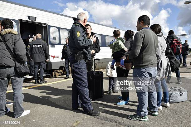 Refugees mainly from Syria speak with a Danish policeman after arriving in Rodby southern Denmark from Germany on September 7 2015 Europe's migrant...