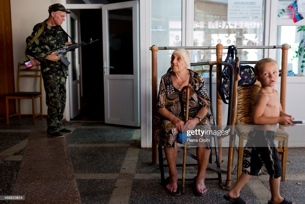 Refugees occupy a building of the National University of Donetsk as shelter from conflict as a pro Russian rebel stands by August 12, 2014 in Donetsk, Ukraine. An estimated of 1200 refugees from the Donestk region fled their home during fights between pro Russian rebels and Ukrainian forces and found shelter in buildings in the university.