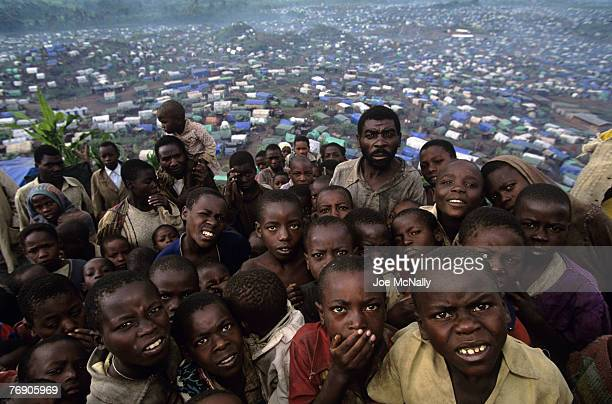 Refugees of Rwanda pose atop a hill looking out on hundreds of makeshift homes in December of 1996 in Zaire In 1994 Rwanda saw one of the worlds...