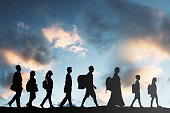 Silhouette Of Refugees People With Luggage Walking In A Row