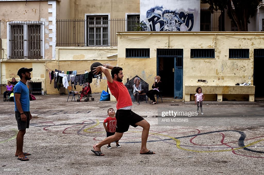 Refugees play at the yard of an abandoned school used by volunteers for hosting families of refugeees from Syria and Afghanistan in Athens on June 27, 2016. / AFP / ARIS