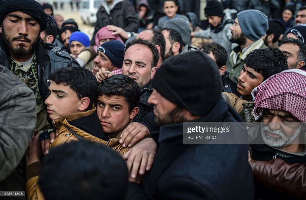 Refugees push each other as they wait for tents as Syrians fleeing the northern embattled city of Aleppo wait on February 6, 2016 in Bab-Al Salam, near the city of Azaz, northern Syria, near the Turkish border crossing. Thousands of Syrians were braving cold and rain at the Turkish border Saturday after fleeing a Russian-backed regime offensive on Aleppo that threatens a fresh humanitarian disaster in the country's second city. Around 40,000 civilians have fled their homes over the regime offensive, according to the Syrian Observatory for Human Rights monitor. / AFP / BULENT KILIC